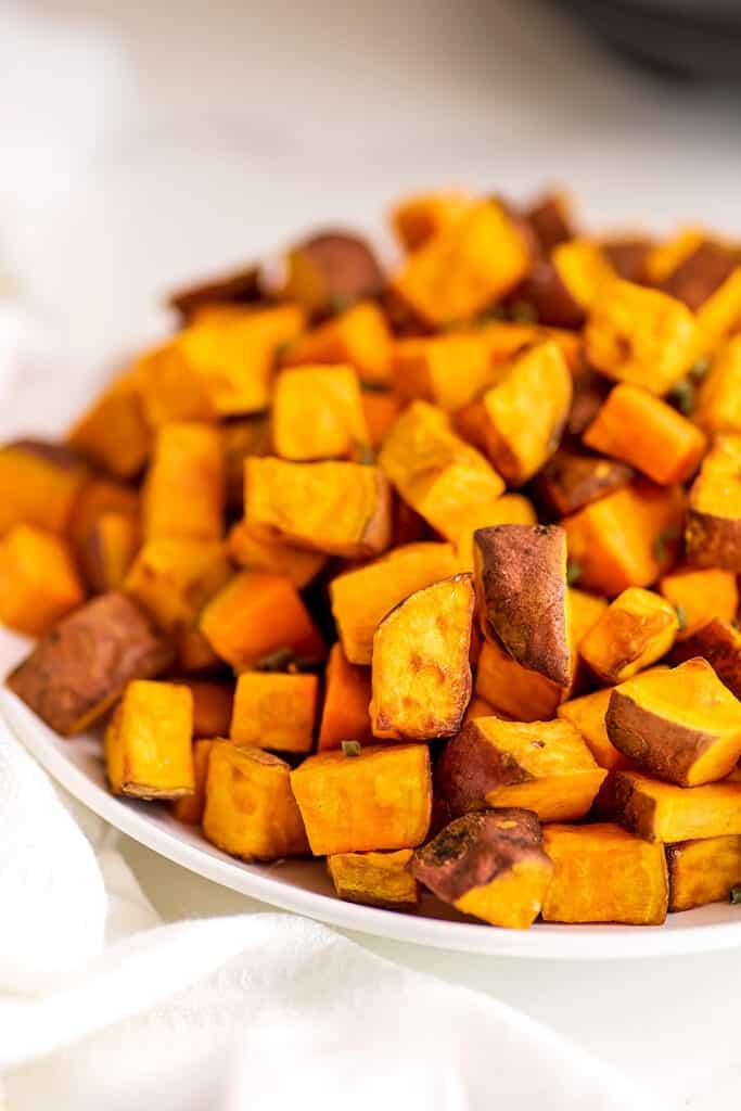 Air fryer sweet potato cubes in white bowl.