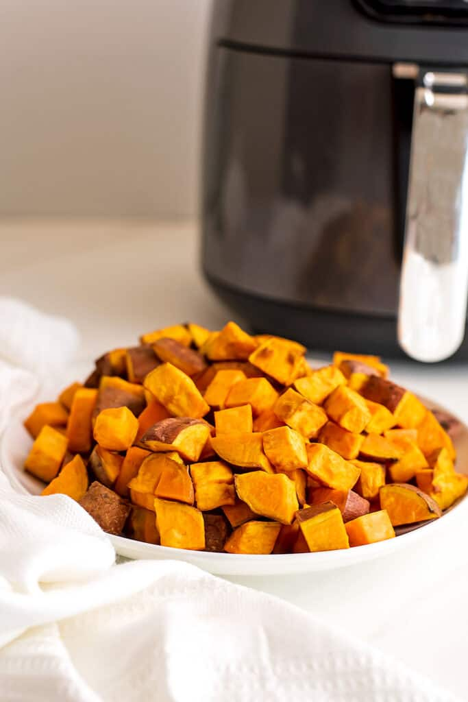 Sweet potato cubes in white bowl, air fryer in background.
