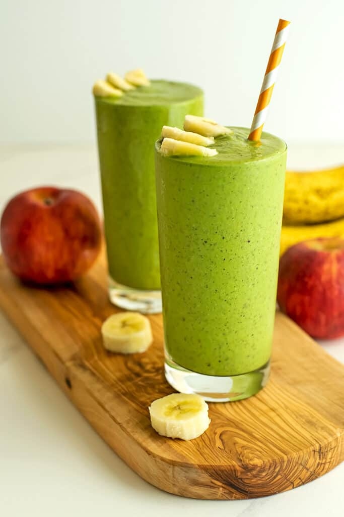 Two glasses full of spinach apple banana smoothies.