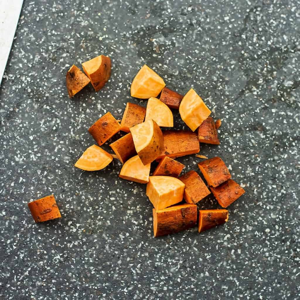 Sweet potatoes being chopped into 1/2 inch cubes for the hash.