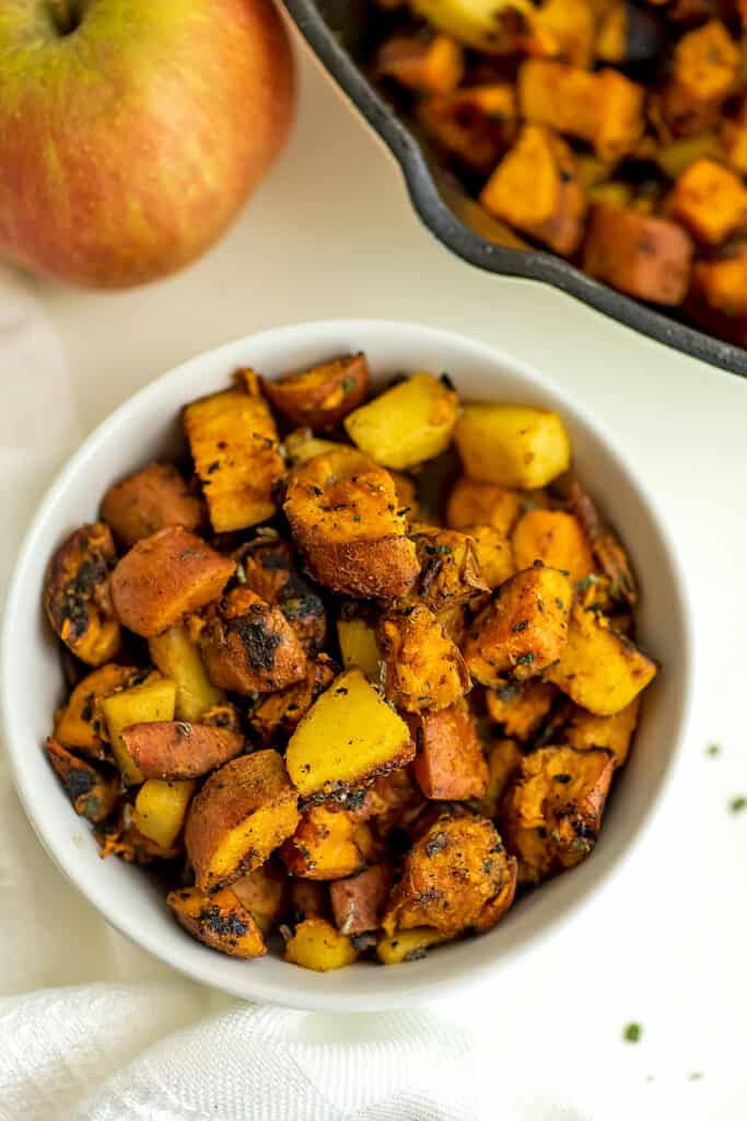White bowl filled with sweet potato apple hash.