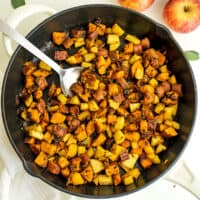 Cast iron skillet filled with apple sweet potato hash, spoon in skillet.