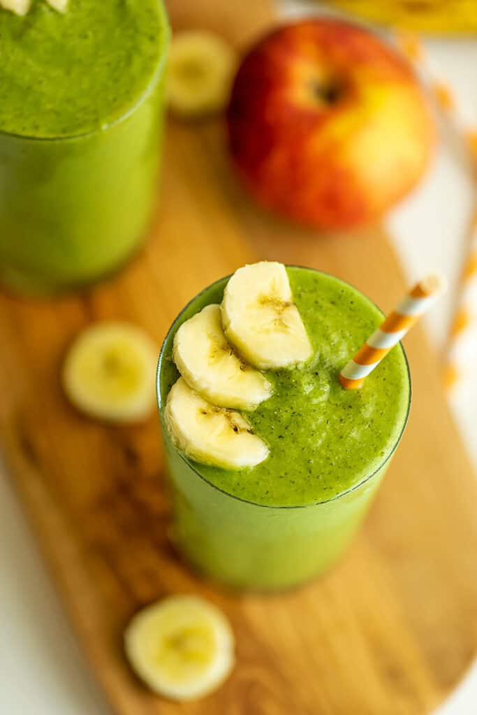 Banana apple spinach smoothie with orange striped straw in cup.