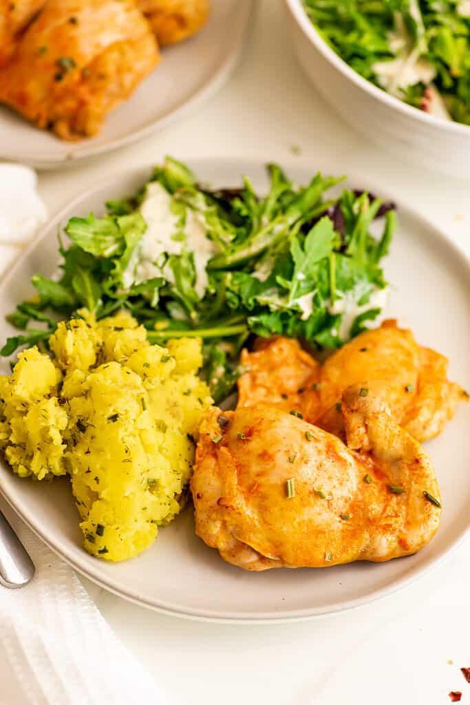 Mashed potatoes, salad and buffalo chicken thighs.