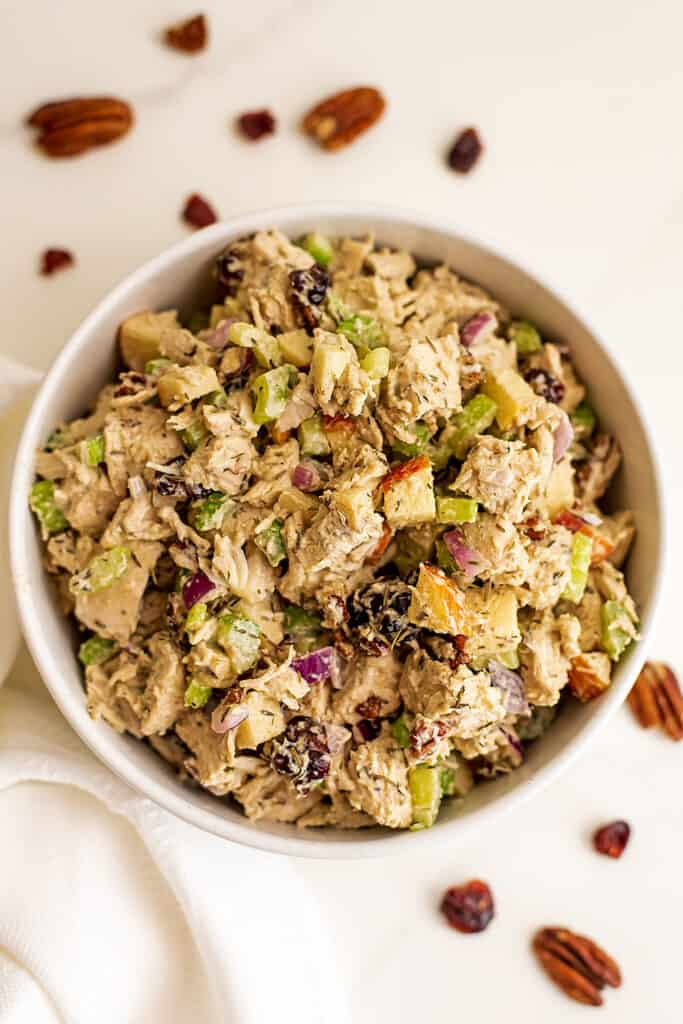 Whole30 chicken salad in a white bowl with cranberries and pecans around bowl.