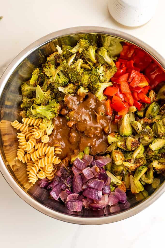 Roasted vegetable pasta salad in silver bowl before stirring.