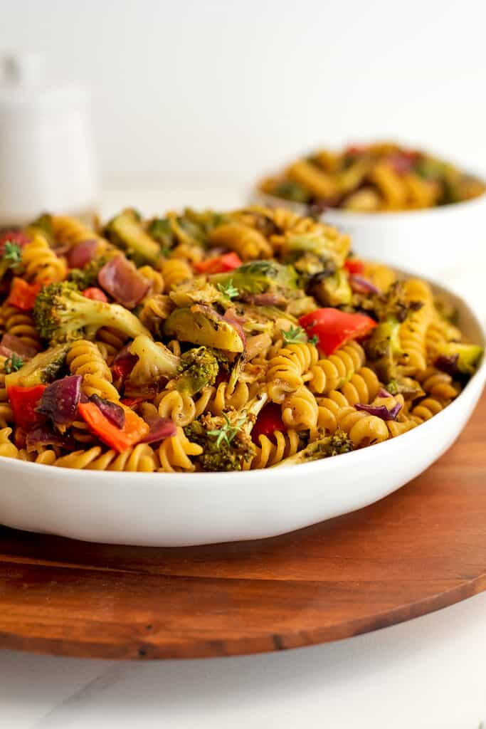 Fall pasta salad in large white bowl with smaller bowl in background.