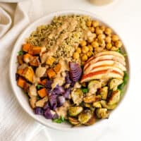 Fall quinoa salad in white bowl with dressing drizzled on top.