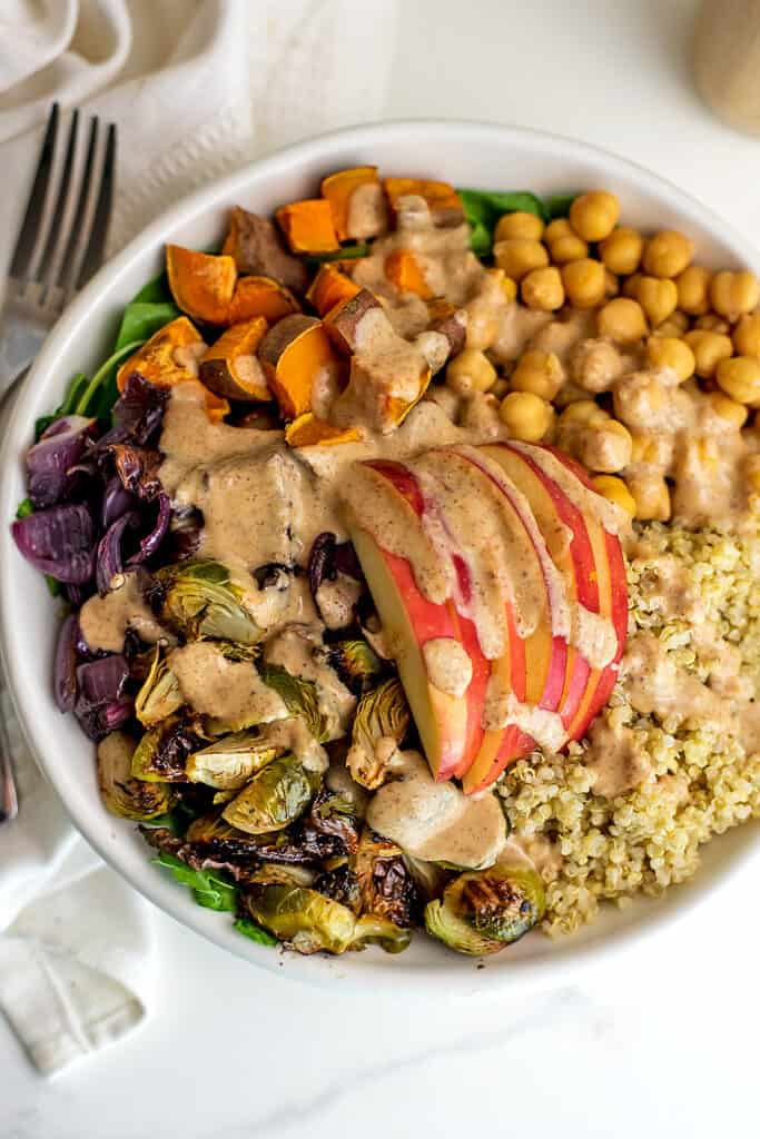 Roasted vegetable quinoa bowl with maple tahini dressing in bowl.