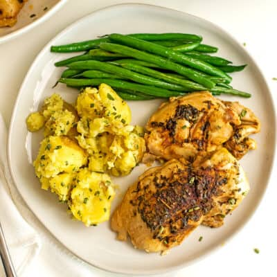 Chicken thighs, smashed potatoes and green beans on a white plate.