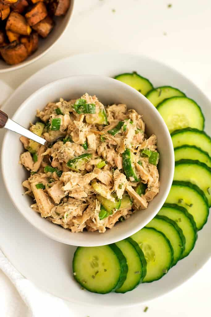 Tuna salad in a bowl with spoon in bowl and cucumbers on plate.