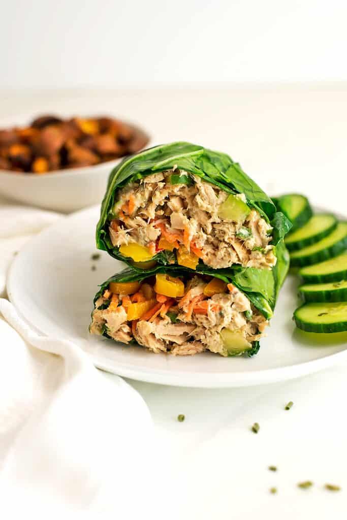 Collard green wrap of tuna salad on a white plate.