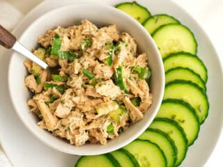 Low FODMAP tuna salad in white bowl on plate with sliced cucumbers.