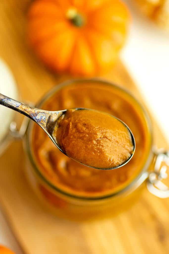 Spoonful of maple pumpkin butter over jar.