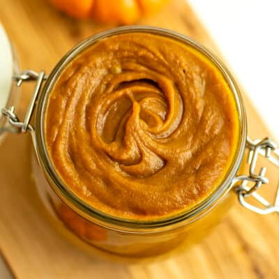 Maple pumpkin butter in a glass jar with silver hinges.