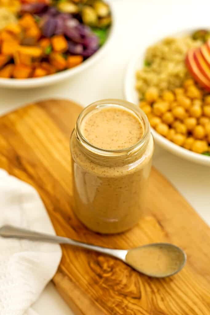 Maple tahini dressing in glass jar on wooden platter.