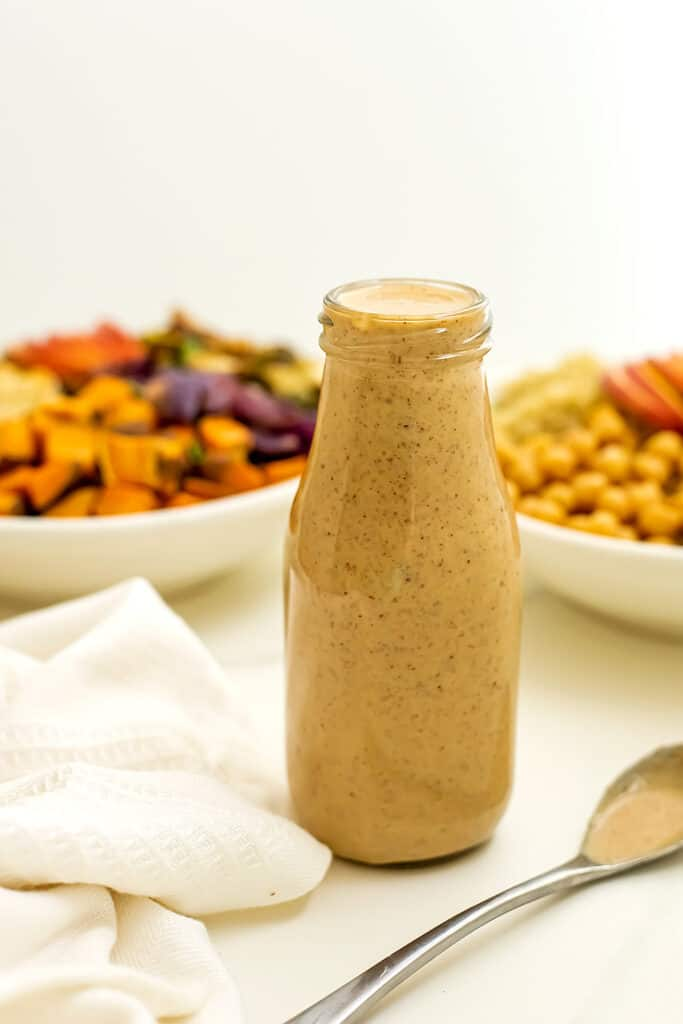 Maple tahini dressing in a bottle in front of salad bowls.