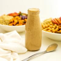 Bottle of maple tahini dressing with spoon in front of bottle.