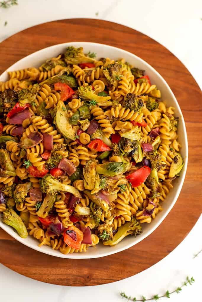 Bowl filled with roasted veggie pasta salad on wooden plate.