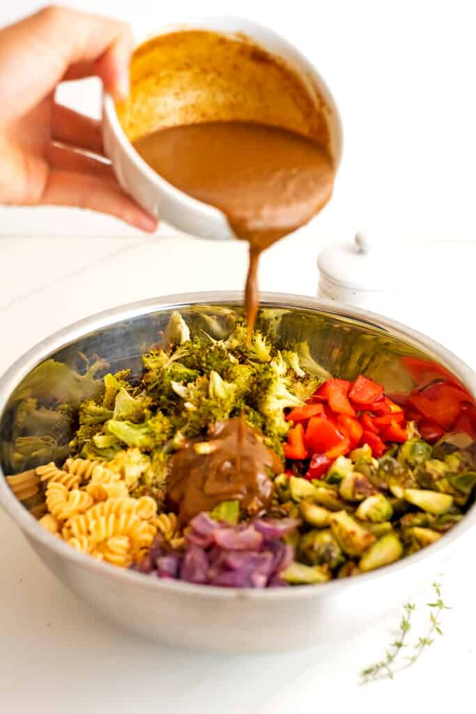 Creamy balsamic dressing being poured over the pasta salad.
