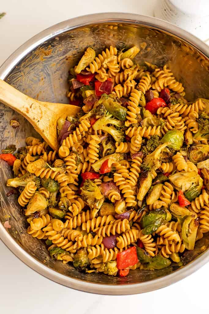 Pasta salad with roasted vegetables in silver bowl after stirring.