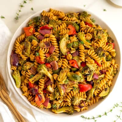Roasted veggie pasta salad in white bowl with spoon on side.
