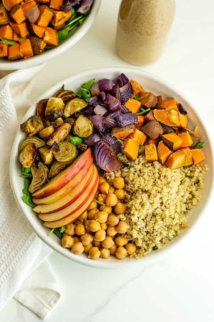 Warm harvest salad in a white bowl without dressing.