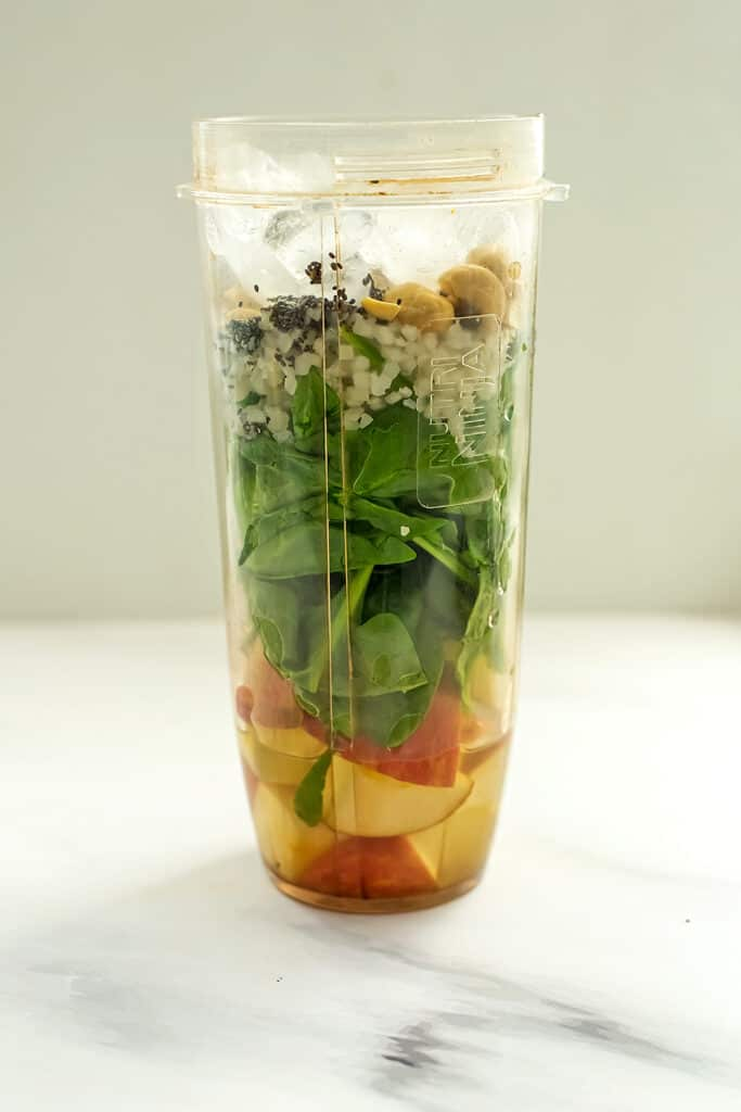 Apple banana spinach smoothie in blender cup before blending.