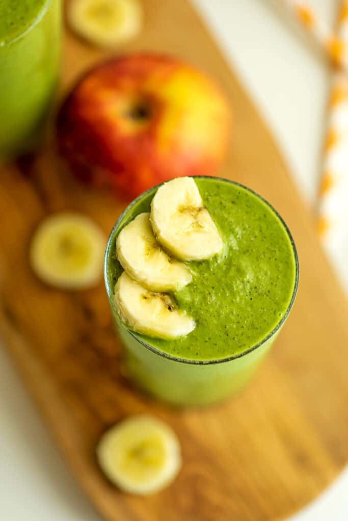 Spinach apple banana smoothie on a wooden trivet.