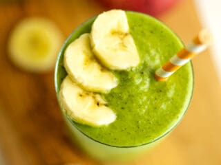 Apple banana spinach smoothie in glass with straw and banana on top.