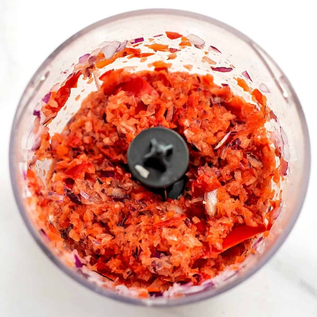 Red bell pepper and red onion in food processor.