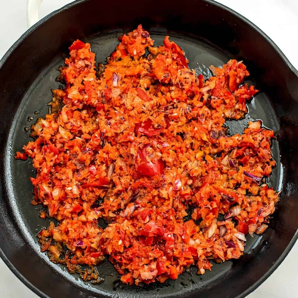 Chopped bell pepper and onion in cast iron skillet before cooking.