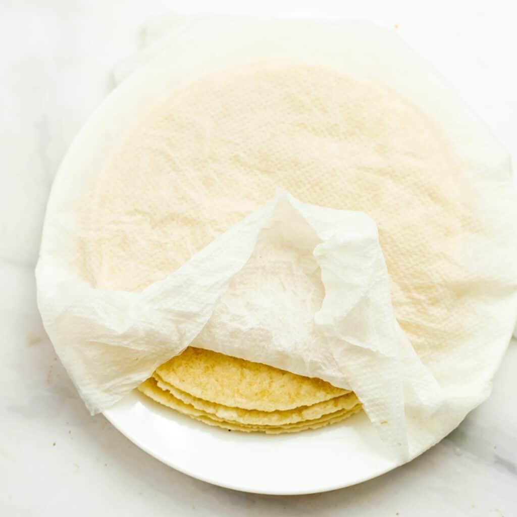Damp paper towel over tortillas.