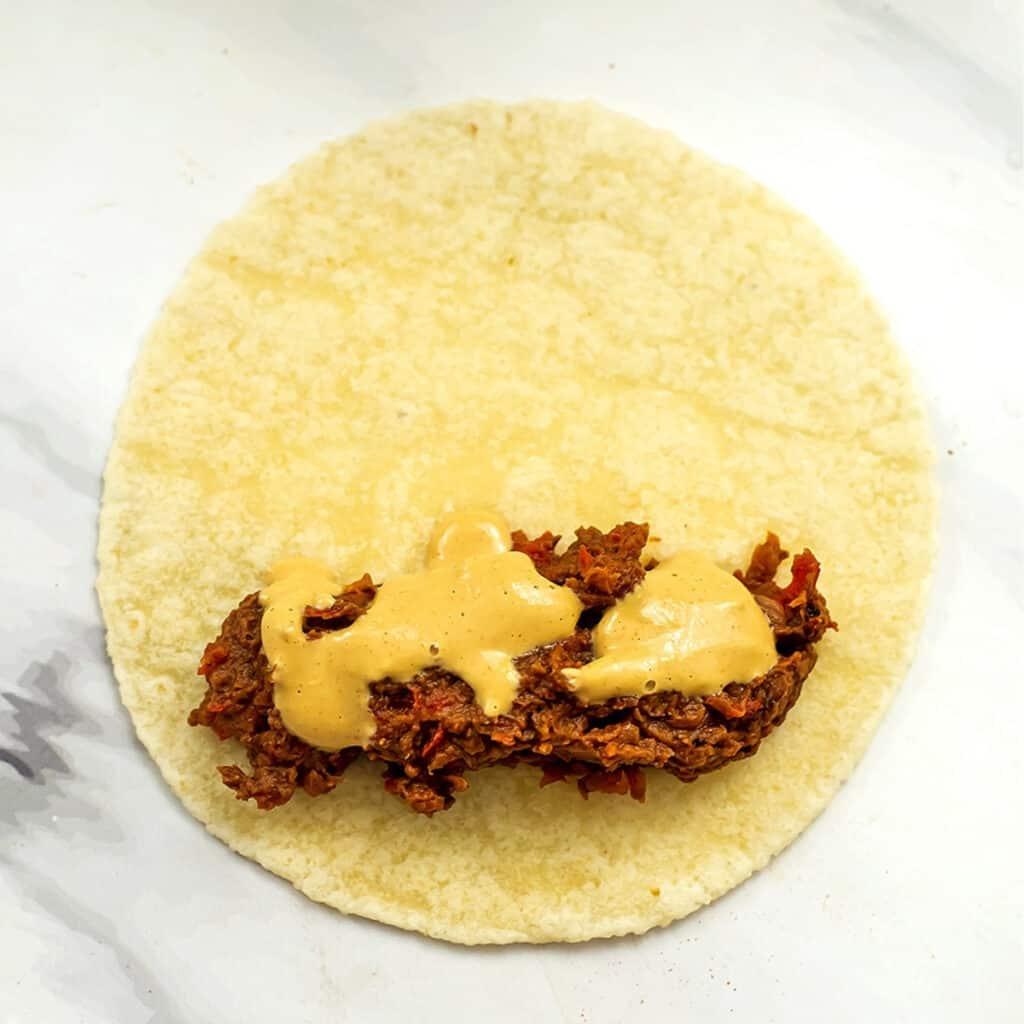Black bean filling with vegan nacho cheese on tortilla.