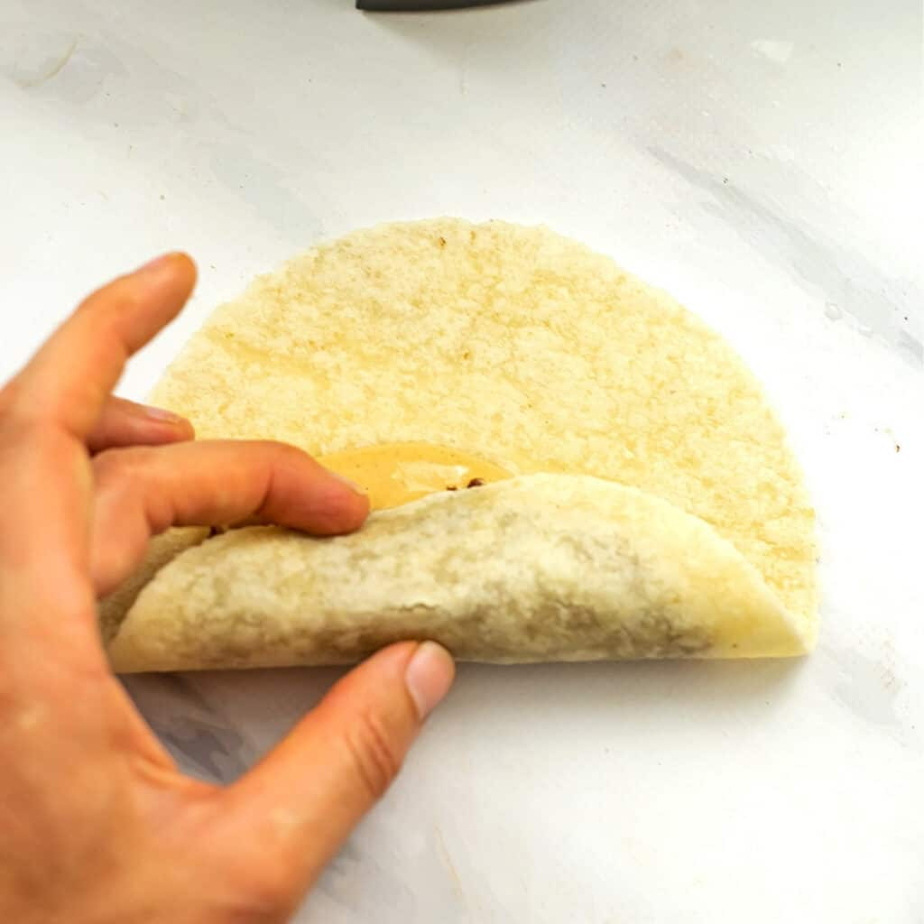 Hand rolling a vegan taquito.