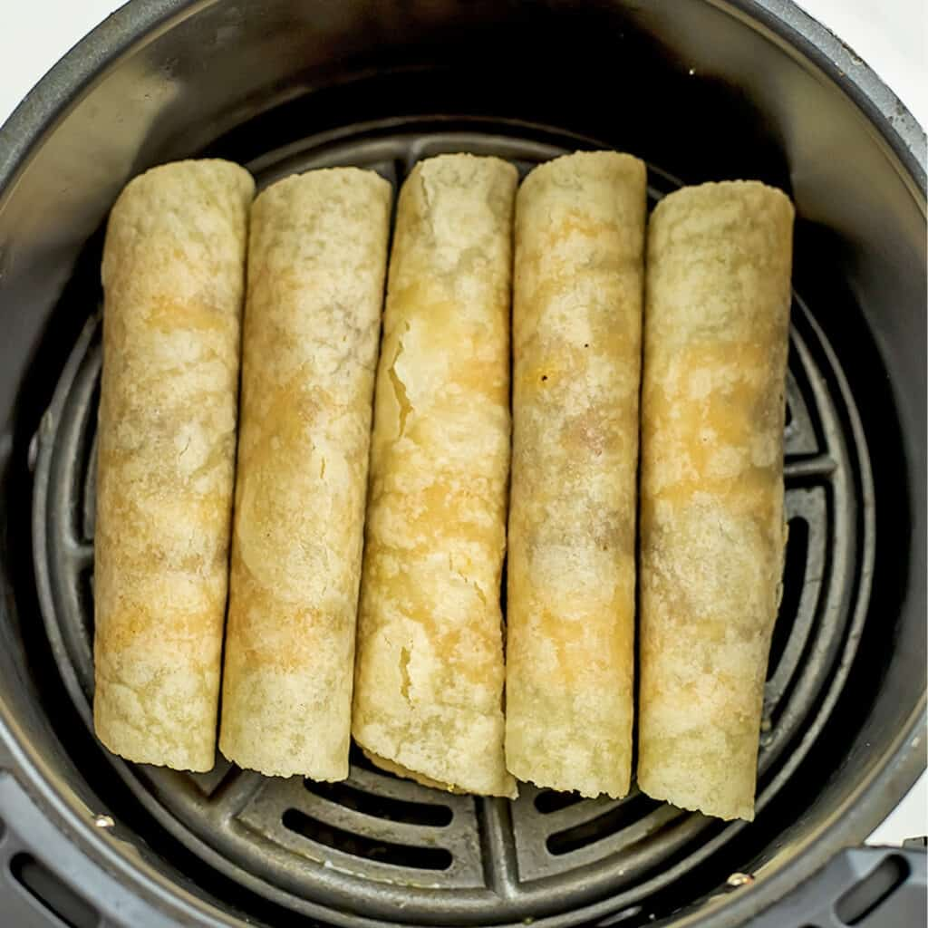 Vegan taquitos in air fryer before cooking.