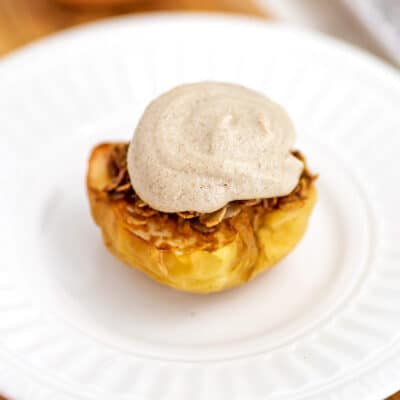 Air fried apple topped iwth frosting on a white plate.