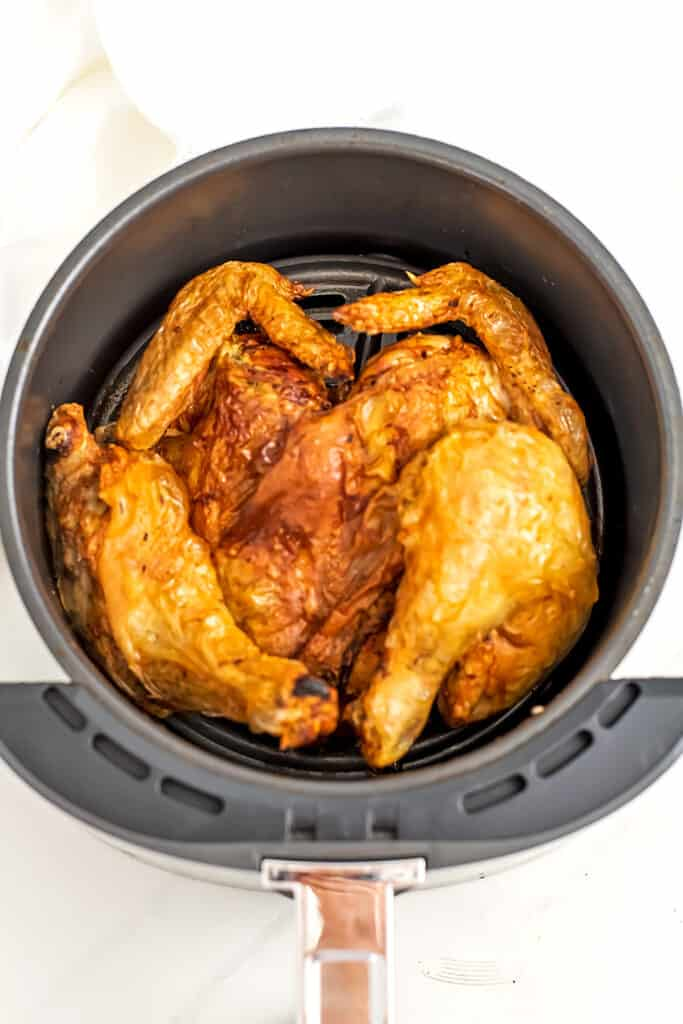 Air fryer basket with spatchcock chicken.