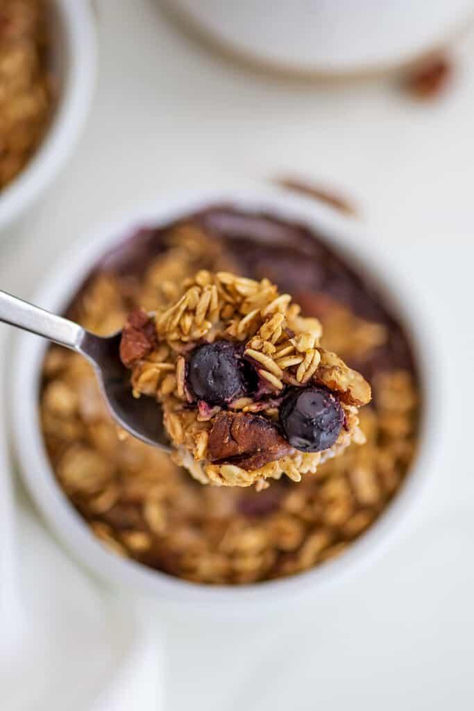 Spoon holding blueberry pecan baked oats over single ramekin.
