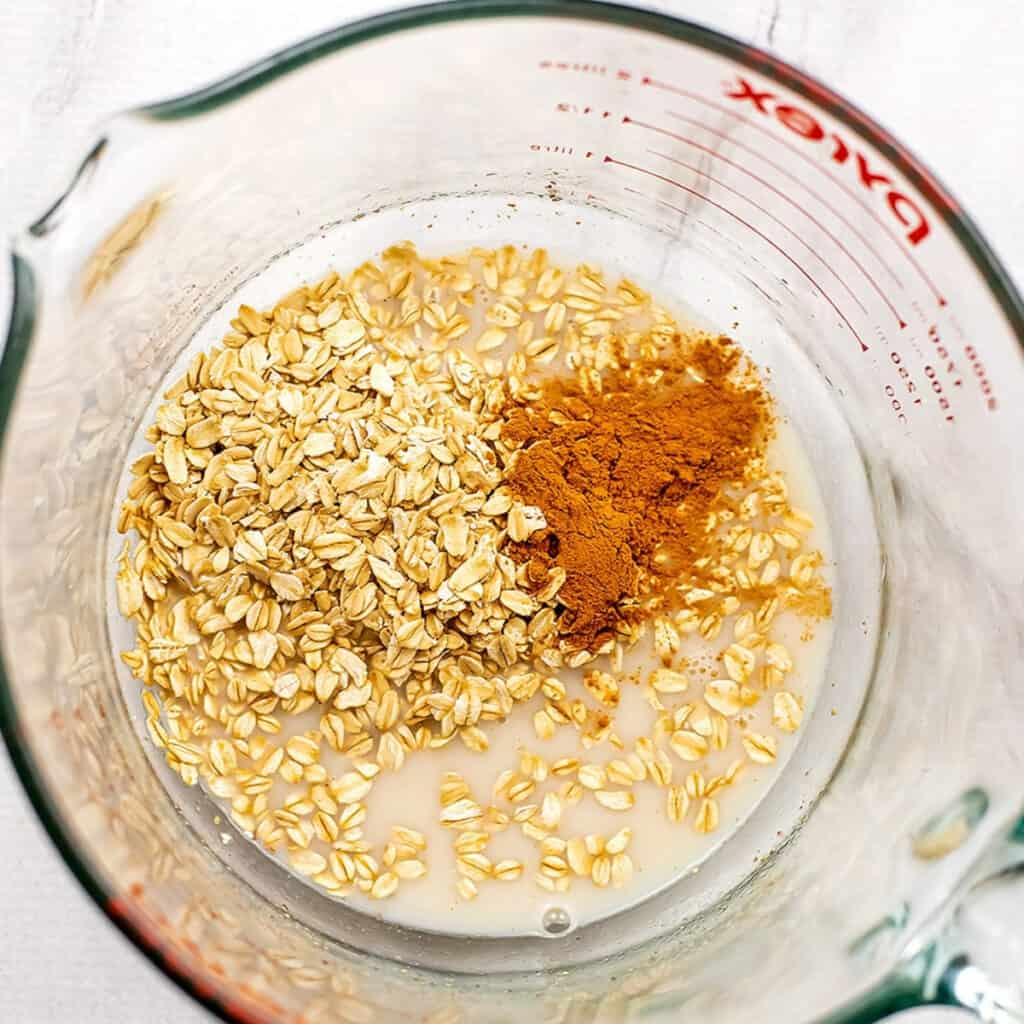 Oats and cinnamon added to dairy free milk mixture in glass mixing bowl.