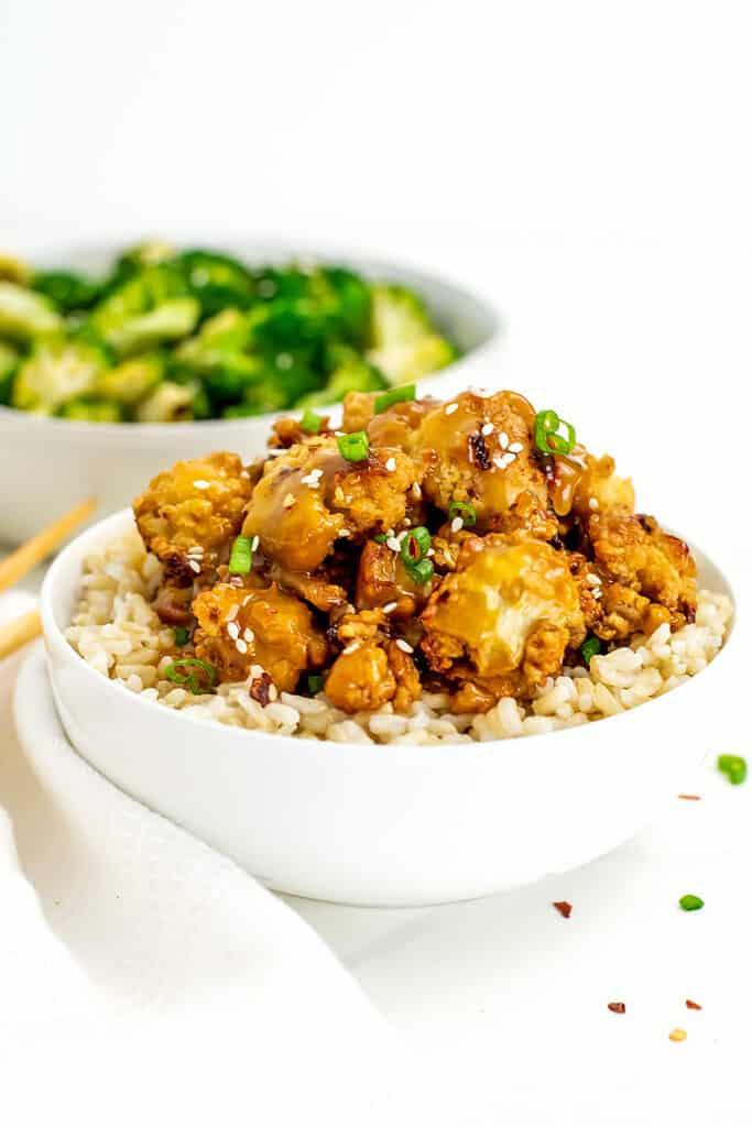 Vegan orange chicken on jasmine rice in a bowl.