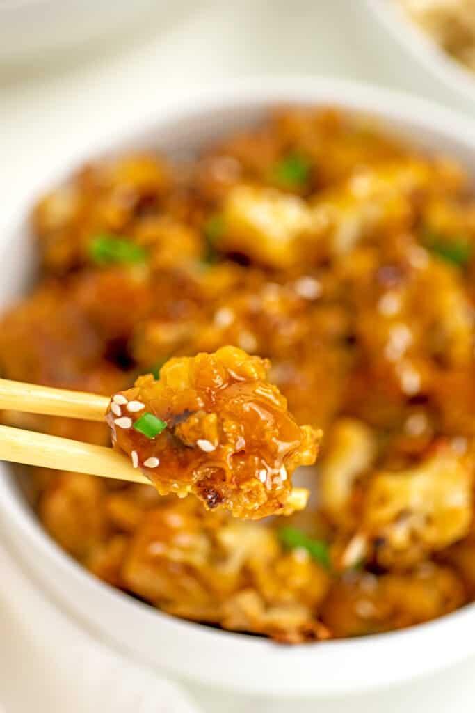 Vegan orange chicken in a bowl with chopsticks picking up a piece.