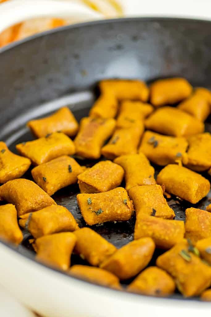 Crispy vegan pumpkin gnocchi in skillet after cookng.